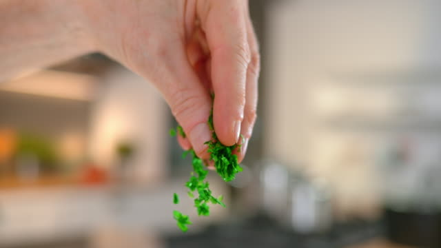 SLO MO TD Person's fingers sprinkling chopped parsley