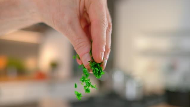 vidéos et rushes de les doigts de slo mo td person saupoudrent de persil haché - plante aromatique