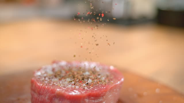 SLO MO TD Person's fingers sprinkling ground pepper onto a piece of red meat Slow motion medium tilt down shot of a person sprinkling ground pepper on a piece of red meat. Shot in Slovenia. spice stock videos & royalty-free footage