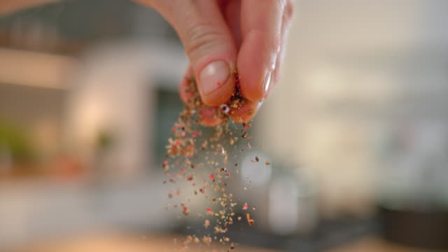 SLO MO LD Person's fingers sprinkling ground pepper Slow motion close up locked down shot of a person's fingers sprinkling ground colourful pepper. Shot in Slovenia. spice stock videos & royalty-free footage