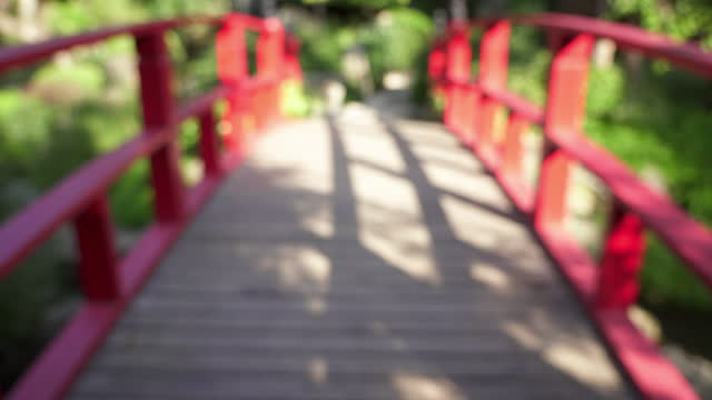 Perspective view of wooden bridge with red railing.