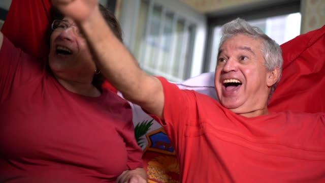 Fan peruana pareja senior viendo partido de fútbol en casa - vídeo