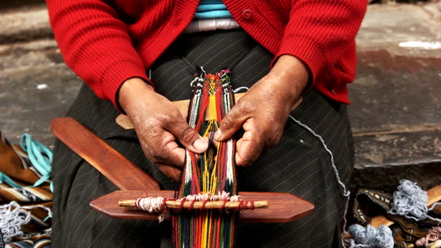 peruvian woman weaving on a street in cusco, peru - prodotto d'artigianato video stock e b–roll