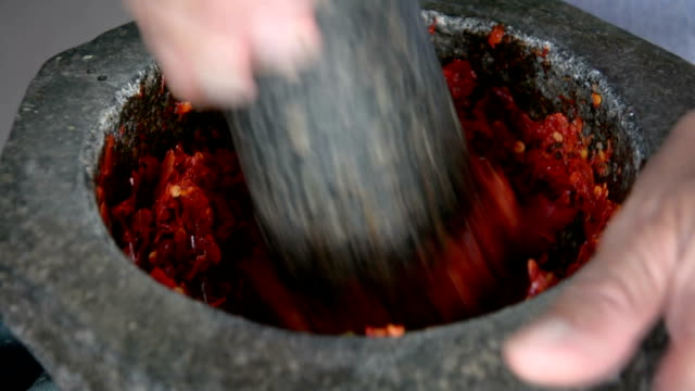 pestling  chilli in motar, Thai cooking. pestling  chilli in motar, Thai cooking. mortar and pestle stock videos & royalty-free footage