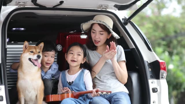 Pet Lover. An Asian family with a mother, daughter and son watching the seaside views on a van. Happy asian children and Mother with shiba inu sitting and Sing Song in car. Pet Lover. An Asian family with a mother, daughter and son watching the seaside views on a van. Happy asian children and Mother with shiba inu sitting and Sing Song in car. land vehicle stock videos & royalty-free footage