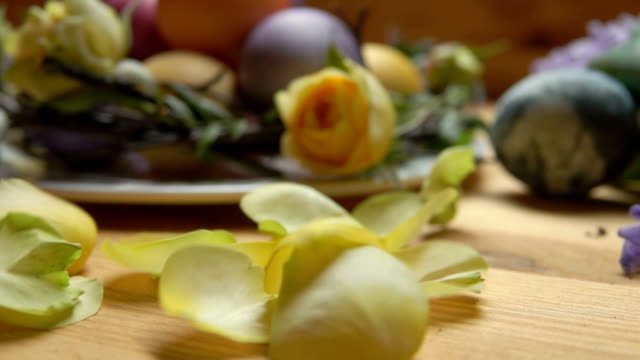 Petals of a yellow rose fall on a table against a background of Easter eggs video