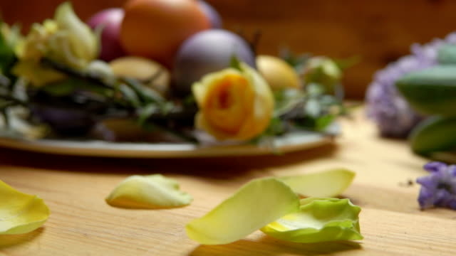 Petals of rose fall on a table against a background of colored Easter eggs video