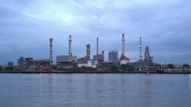 Petrochemical oil refinery and sea in industrial engineering concept in Bangna district, Bangkok, Thailand. Oil and gas tanks pipelines in industry. Modern metal factory.