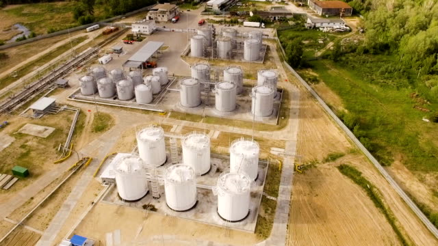 petrol industrial zone with cisterns and tanks on sand. aerial view video