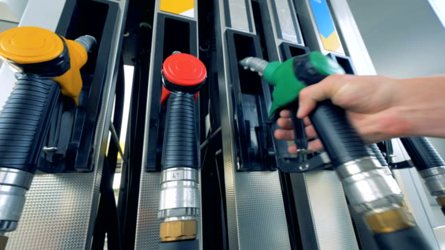 Petrol pistol with green handle is being inserted into the pump Petrol pistol with green handle is being inserted into the pump. 4K refueling stock videos & royalty-free footage