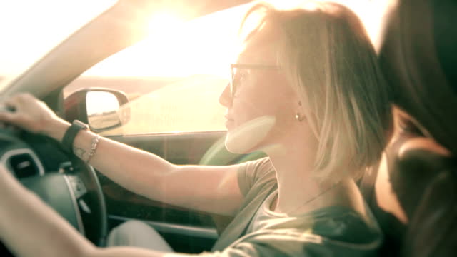 Petty woman driving a car at sunset