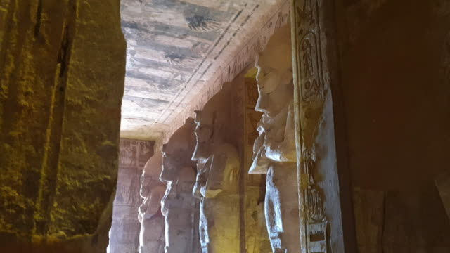 Pharaoh statue columns in row with sun light come in at Abu Simbel Egypt