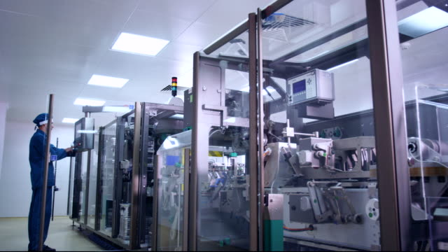 pharmaceutical industry. pharmaceutical worker operating pharmacy equipment - apparecchiatura medica video stock e b–roll