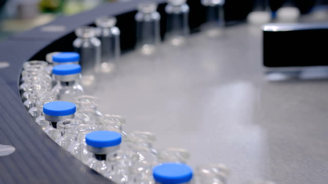 pharmaceutical technology concept - conveyor belt with empty glass bottles - igiene video stock e b–roll