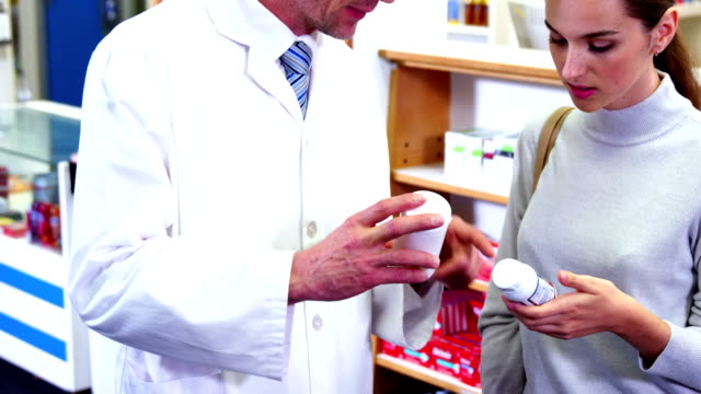 Pharmacist assisting the bottle of drug to customer video