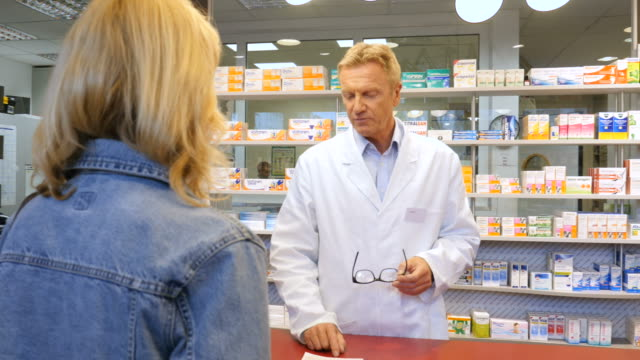 Pharmacist assisting woman with medicine at store Mature pharmacist assisting customer with medicine. Professionals are working together at checkout counter. Woman is leaving after buying prescription from pharmacy. pharmaceutical industry stock videos & royalty-free footage