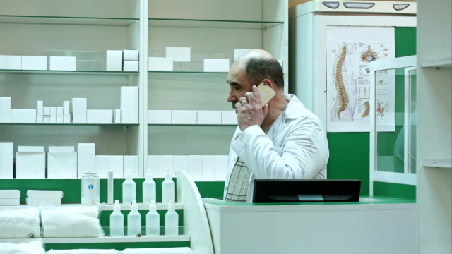 Pharmacist consulting customer via cell phone in drug store video