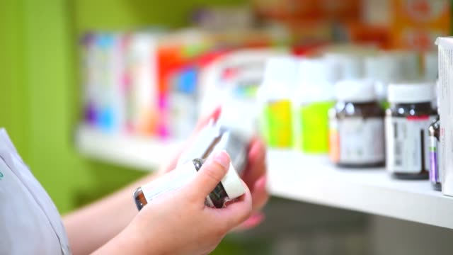 pharmacist hands holding and looking medicine bottles In Pharmacy store