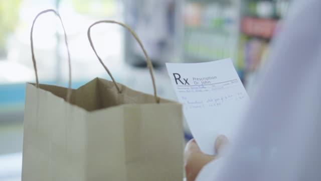 farmacista mette il medicinale nella borsa per il cliente,slow motion - prescrizione medica video stock e b–roll