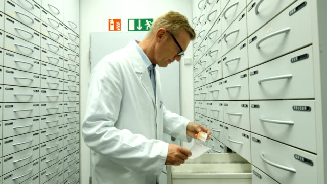 Pharmacist searching medicine in filling cabinets Mature pharmacist reading prescription paper while searching medicine in filing cabinets. Male is working in storage compartment of pharmacy. He is wearing lab coat. storage room stock videos & royalty-free footage