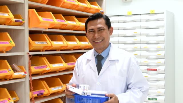 vídeos y material grabado en eventos de stock de sonriendo a la cámara sosteniendo medicamento farmacéutico - encuadre cintura para arriba