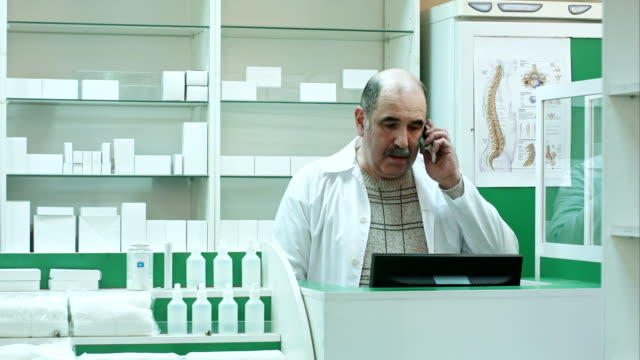Pharmacist talk with client using mobile phone in pharmacy video