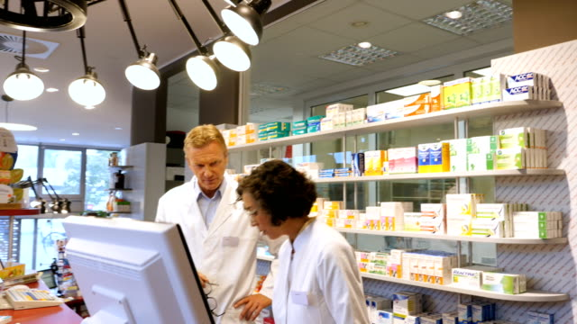 Pharmacist talking to customer over prescription
