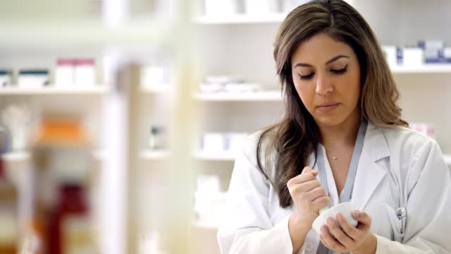 Pharmacist uses mortar and pestle to compound medication Focused female pharmacist uses mortal and pestle to make compounded medication in a specialty pharmacy. complexity stock videos & royalty-free footage