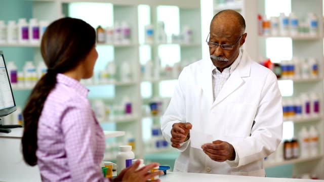 Pharmacist A customer handing a pharmacist an prescription. pharmacist stock videos & royalty-free footage