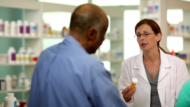 Pharmacist A female pharmacist consulting with a senior couple. pharmacist stock videos & royalty-free footage