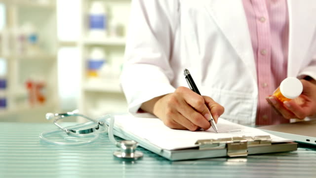 Pharmacist Writting on Clipboard A pharmacist enters information for perscriptions.  pills stock videos & royalty-free footage
