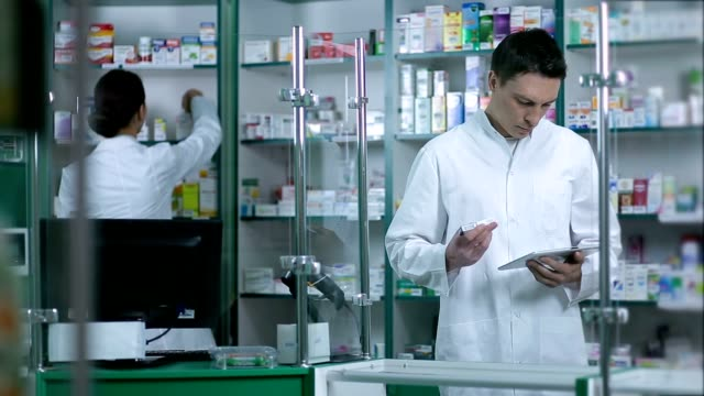 Pharmacists checking medicines at pharmacy video