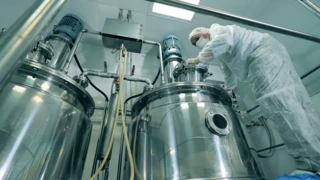 薬理学の専門家は化学反応器と協力しています - 化学点の映像素材/bロール