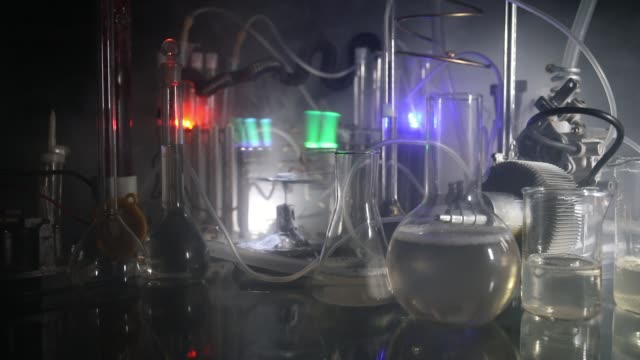 pharmacy and chemistry theme. test glass flask with solution in research laboratory. science and medical background. laboratory test tubes on dark toned background , science research equipment concept - science research stock videos & royalty-free footage