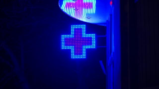 apotek neon blå röda korset tecken på väggen av byggnaden på natten. - korsform bildbanksvideor och videomaterial från bakom kulisserna