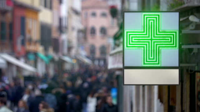 Pharmacy sign with green cross in busy street video