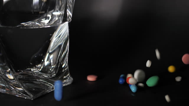 Pharmacy theme. Multicolored Isolated Pills,Capsules on Black Surface near water glass. Vitamins falling on dark surface..Heap of colorful round capsule pills with medicine antibiotic Slow motion video