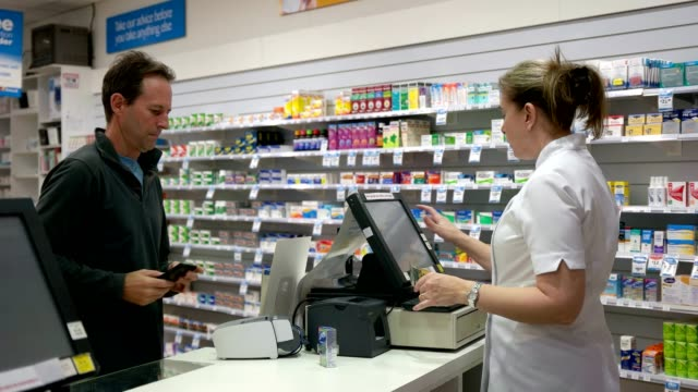 pharmacy transaction a customer purchases a medication from an australian pharmacy pharmaceutical industry stock videos & royalty-free footage