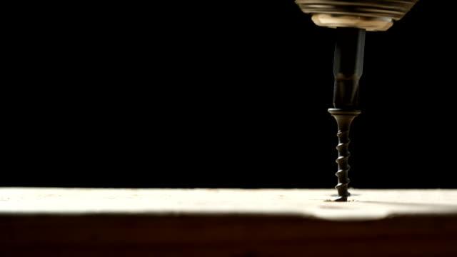 vídeos de stock e filmes b-roll de a phillips screwdriver bit in a power drill chuck drives a black carbon steel screw into a light wood board against a black background - bricolage