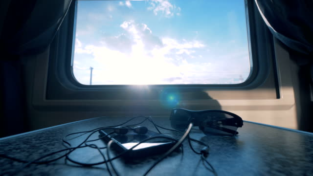Phone and glasses lay on a table near a train window.
