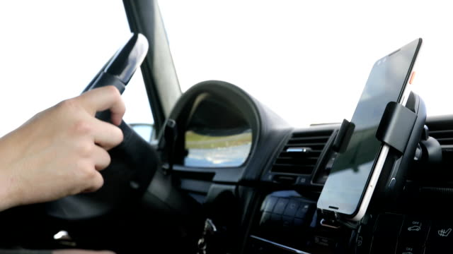 Phone attacked on dashboard for GPS Crop person driving car holding hands on steering wheel with smartphone mounted to dashboard for GPS dashboard vehicle part stock videos & royalty-free footage
