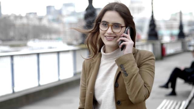 女性の笑みを浮かべて、移動中に電話をかける。 - 美人点の映像素材/bロール