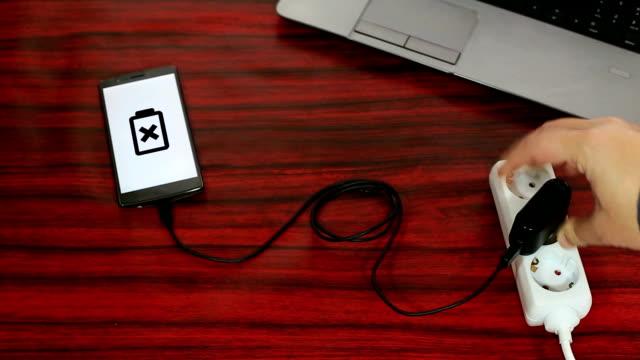 vidéos et rushes de téléphone connecté à une prise électrique sur une bande de puissance grâce à un câble et adaptateur. - vidéos de rallonge électrique