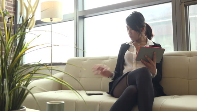 Phone Conversation With Beautiful Asian Woman Using Ipad At Home video