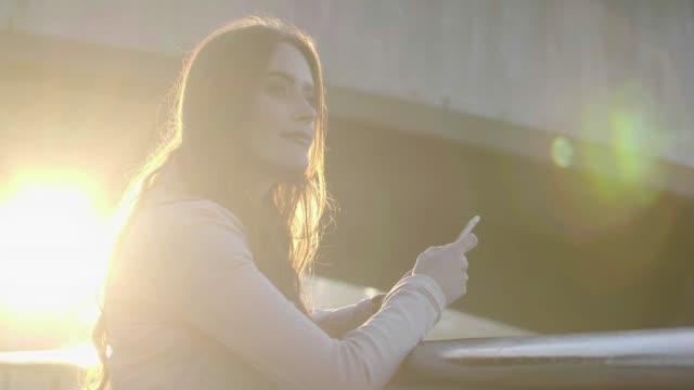 telefon meddelande, vacker enda kvinna utomhus, lins flare. - telefonmeddelande bildbanksvideor och videomaterial från bakom kulisserna