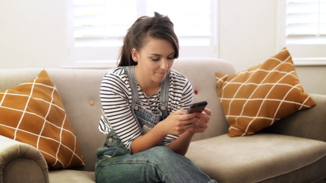 Phone message, sofa. Single young woman. DS. Young woman in 20s text messaging sitting on a sofa in a modern room. Her fingers a busy writing a message, as the camera moves across and slightly back, she folds her arm across herself happy that she has sent her message and gently smiles. DS sofa stock videos & royalty-free footage