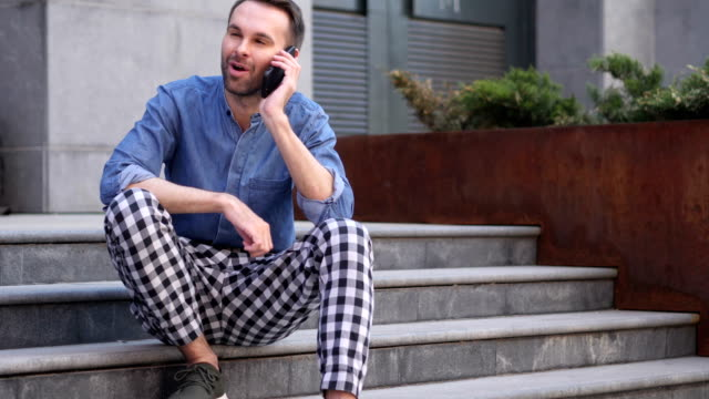 Phone Talk, Man Attending Call while Sitting on Stairs Outside Building video