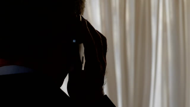 電話の盗聴: 男の陰で携帯電話に話す - 腐敗点の映像素材/bロール