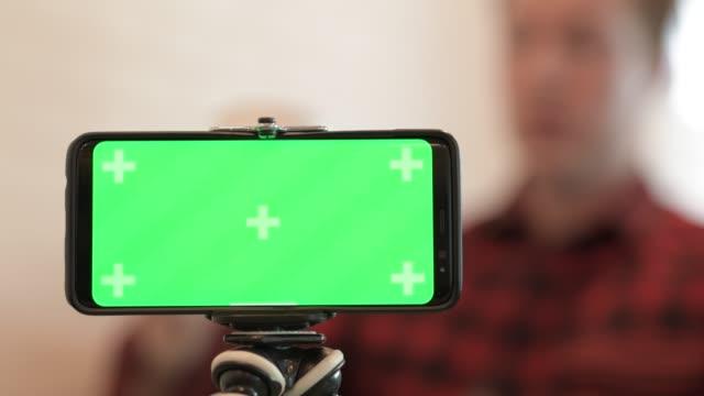 telefon med grön skärm mot unga hipster man i bakgrunden - endast en man i 30 årsåldern bildbanksvideor och videomaterial från bakom kulisserna