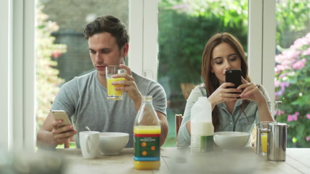phones at breakfast Stock movie clip of a young couple sitting at the breakfast table, not speaking to each other but fully engaged with their phones. ignoring stock videos & royalty-free footage